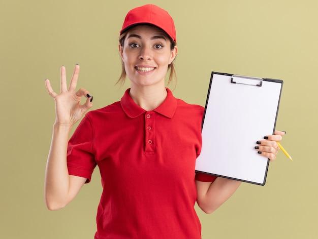 Улыбающаяся молодая симпатичная доставщица в униформе держит буфер обмена и карандаш, жестикулируя знак рукой на оливково-зеленом