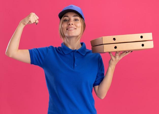 制服を着た笑顔の若いかわいい配達の女の子はピザの箱を保持し、ピンクの上腕二頭筋を緊張させる