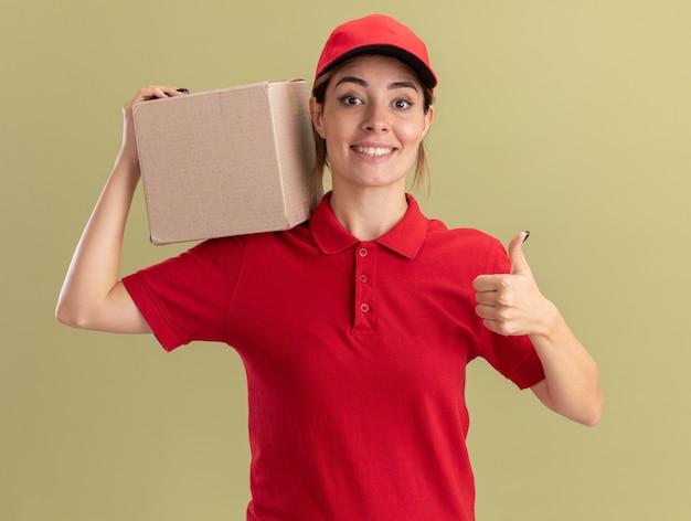 Улыбающаяся молодая симпатичная доставщица в униформе показывает палец вверх и держит картонную коробку на плече на оливково-зеленом
