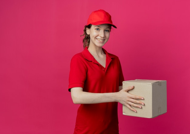 Smiling young pretty delivery girl in red uniform and cap holding carton box isolated on crimson background with copy space