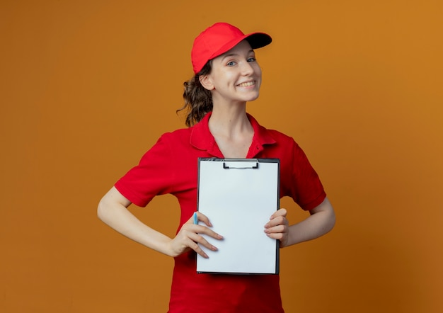 Smiling young pretty delivery girl in red uniform and cap holding pen and showing clipboard at camera isolated on orange background with copy space
