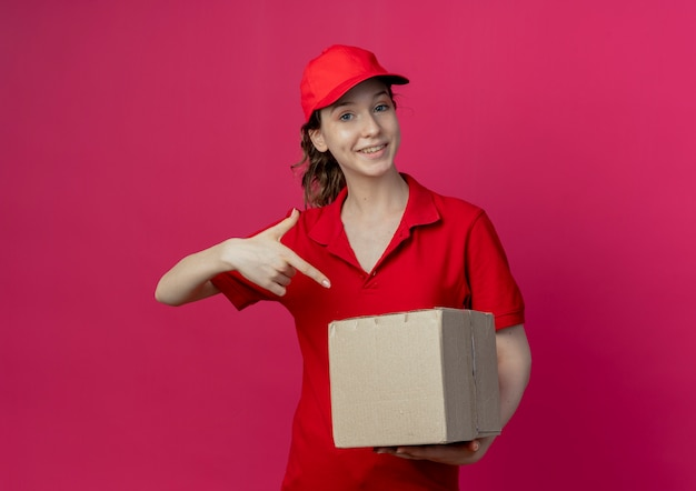 Smiling young pretty delivery girl in red uniform and cap holding and pointing at carton box isolated on crimson background with copy space