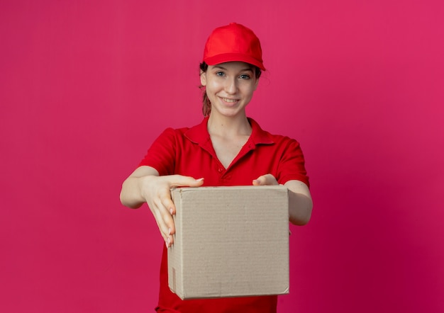 Smiling young pretty delivery girl in red uniform and cap stretching out carton box at camera isolated on crimson background with copy space