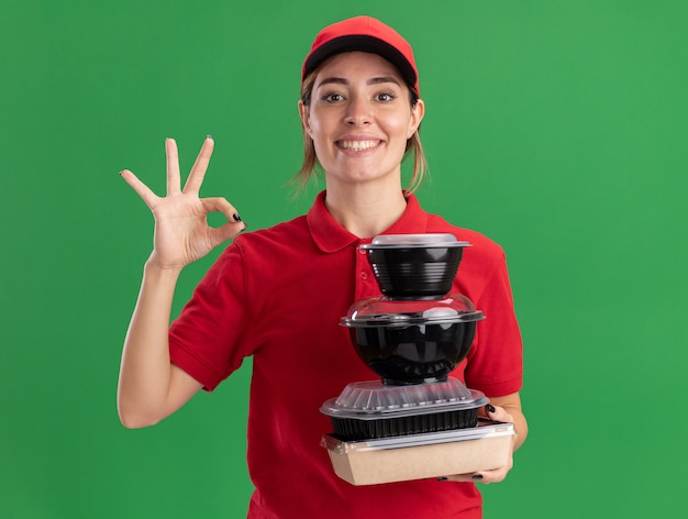Sorridente giovane bella ragazza di consegna in gesti uniformi segno ok con la mano e tiene i contenitori per alimenti sul pacchetto alimentare sul verde