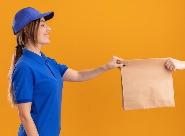 La giovane ragazza graziosa sorridente di consegna in uniforme dà il pacchetto di carta a qualcuno sull'arancia