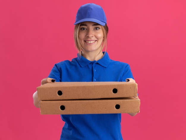 Sorridente giovane bella ragazza di consegna in uniforme che tiene scatole per pizza sul rosa