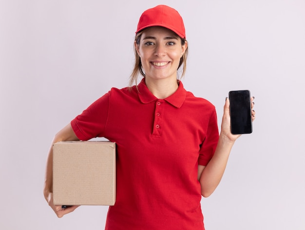 Smiling young pretty delivery girl in uniform holds cardbox and phone on white