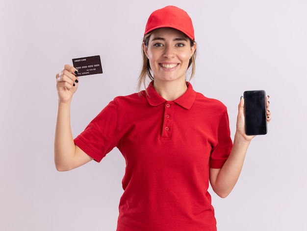 Smiling young pretty delivery girl in uniform holds credit card and phone on white