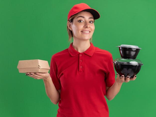 La giovane ragazza graziosa di consegna sorridente in uniforme tiene i contenitori per alimenti e il pacchetto alimentare sul verde