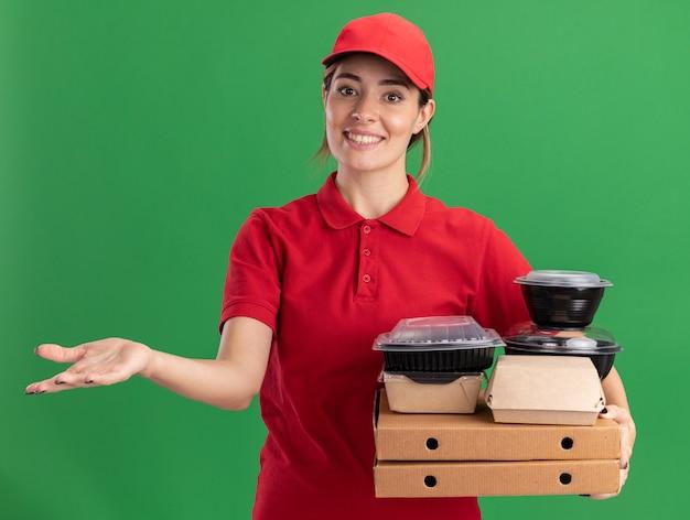 Sorridente giovane bella ragazza di consegna in uniforme tiene detiene confezioni di carta per alimenti e contenitori su scatole per pizza
