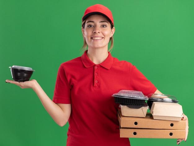 La giovane ragazza graziosa di consegna sorridente in uniforme tiene i pacchetti e i contenitori di cibo di carta sulle scatole della pizza che guarda l'obbiettivo sul verde