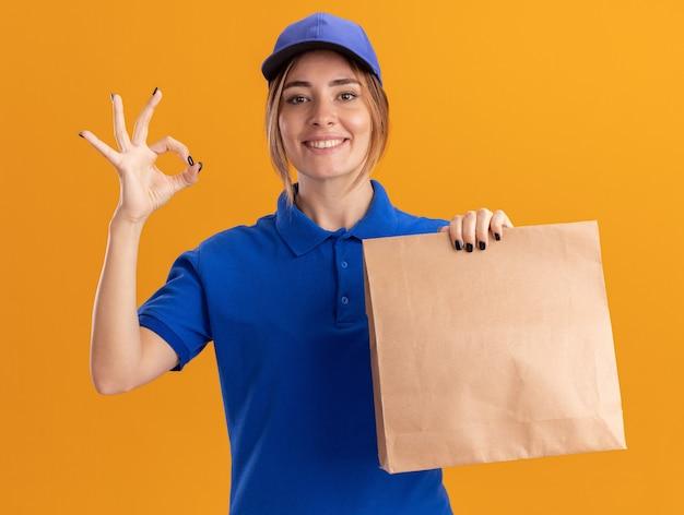 La giovane ragazza graziosa di consegna sorridente in uniforme tiene il pacchetto di carta e gesti il segno giusto della mano sull'arancia