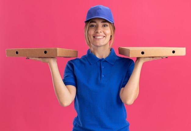 Sorridente ragazza graziosa giovane consegna in uniforme tiene scatole per pizza su due mani sul rosa