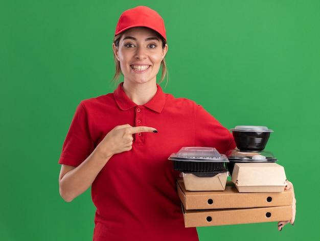 Sorridente giovane bella ragazza di consegna in uniforme tiene e indica confezioni di carta per alimenti e contenitori su scatole per pizza su verde