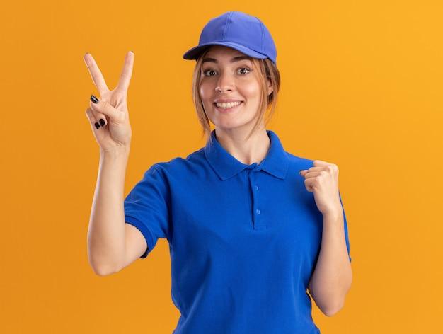 Sorridente giovane bella ragazza di consegna in uniforme mantiene pugno e gesti il segno della mano di vittoria sull'arancio