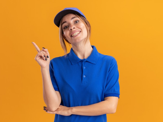 Sorridente giovane ragazza graziosa di consegna in punti uniformi a lato su arancione