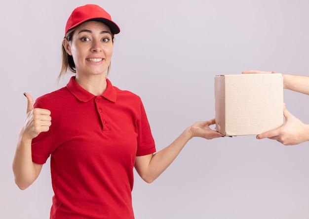 Sorridente giovane ragazza graziosa di consegna in uniforme thumbs up e dà cardbox a qualcuno su bianco