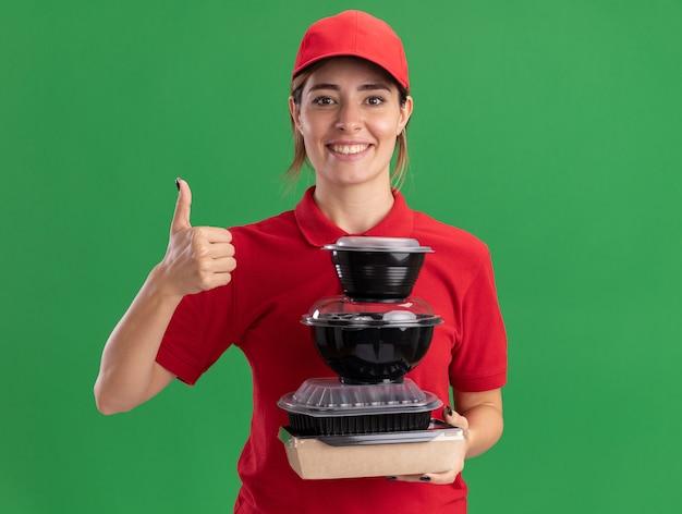 Sorridente giovane bella ragazza di consegna in uniforme pollice in alto e tiene i contenitori per alimenti sul pacchetto alimentare sul verde