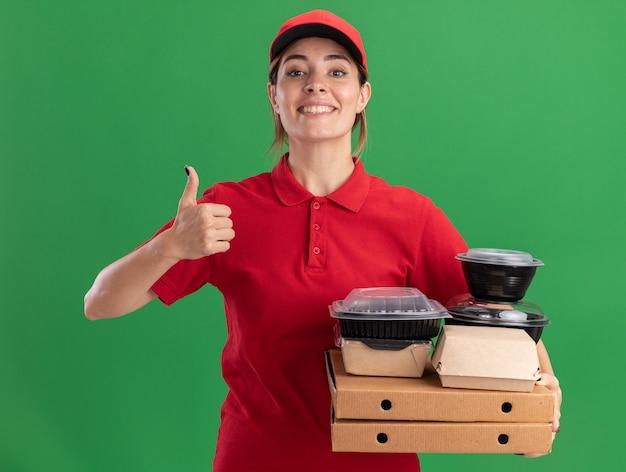 Sorridente giovane bella ragazza di consegna in uniforme pollice in alto tiene i pacchetti di cibo di carta e contenitori su scatole per pizza