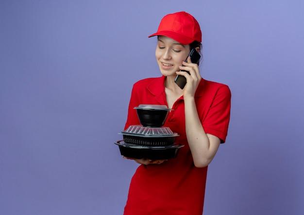 Sorridente giovane bella ragazza delle consegne che indossa l'uniforme rossa e il berretto che tiene e guarda i contenitori per alimenti e parla al telefono