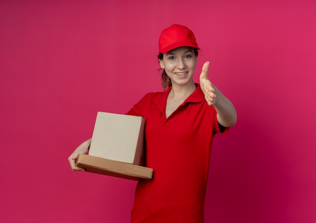 Smiling young pretty delivery girl wearing red uniform and cap holding pizza package and carton box stretching out hand towards camera gesturing hi isolated on crimson background with copy space