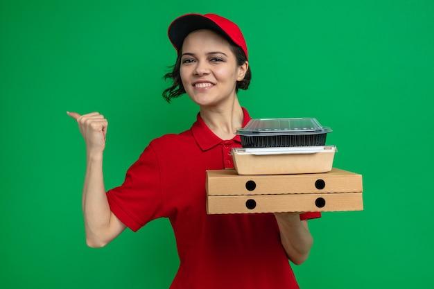 Sorridente giovane graziosa donna di consegna che tiene in mano un contenitore per alimenti con imballaggio su scatole per pizza e che punta a lato
