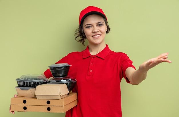 Sorridente giovane graziosa donna delle consegne che tiene in mano contenitori per alimenti con imballaggi su scatole per pizza e tiene la mano aperta