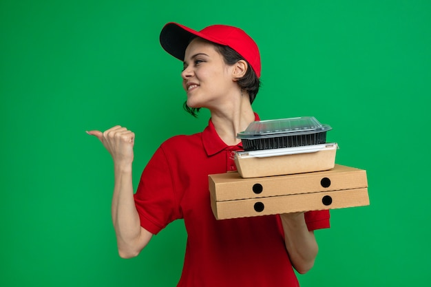 Sorridente giovane bella donna delle consegne che tiene contenitori per alimenti con imballaggi su scatole per pizza guardando e puntando a lato