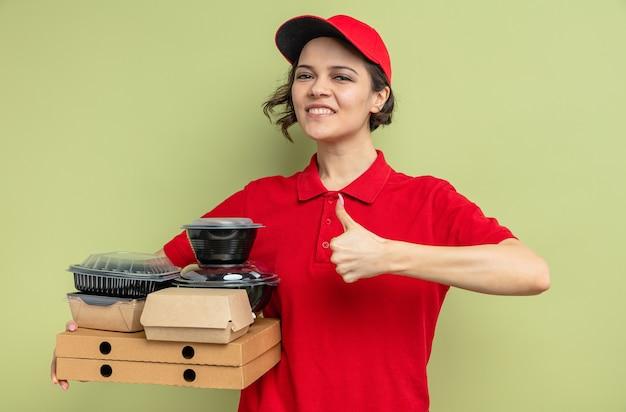 Sorridente giovane graziosa donna delle consegne che tiene in mano contenitori per alimenti con imballaggi su scatole per pizza e sfogliando