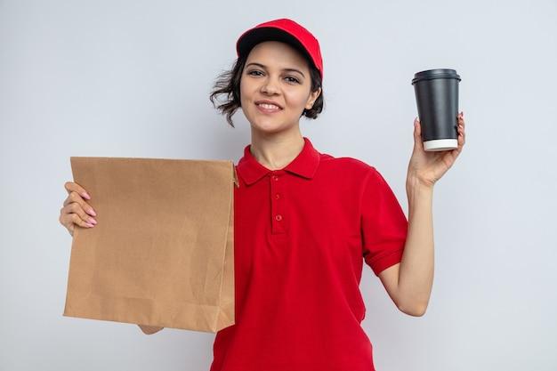 Sorridente giovane graziosa donna di consegna che tiene in mano imballaggi per alimenti di carta e tazza da asporto