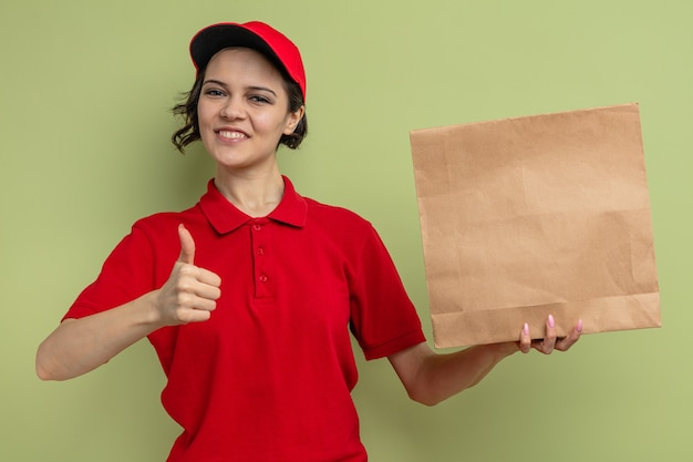 Smiling young pretty delivery woman holding paper food packaging and thumbing up