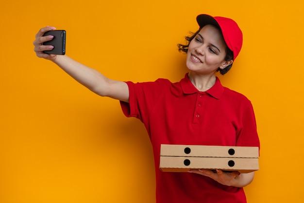 웃고 있는 젊고 예쁜 배달부 여성이 피자 상자를 들고 전화로 셀카를 찍고 있다