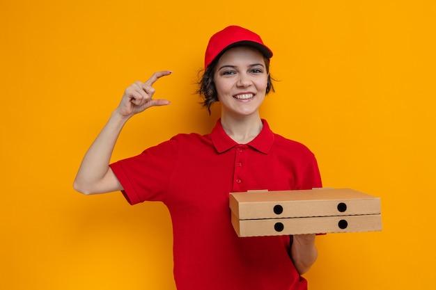 Sorridente giovane graziosa donna delle consegne che tiene in mano scatole per pizza e finge di tenere qualcosa