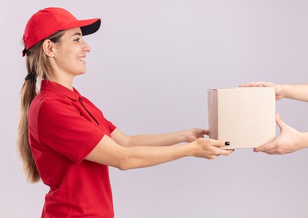 制服を着た若いかわいい配達の女性の笑顔は、白い壁に隔離された誰かにカードボックスを与えます
