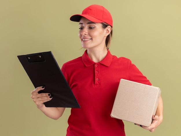 制服を着た笑顔の若いかわいい配達の女性は、カードボックスを保持し、分離されたクリップボードを見て