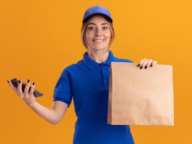 Улыбающаяся молодая красивая женщина-доставщик в униформе держит бумажный пакет и телефон, изолированные на оранжевой стене
