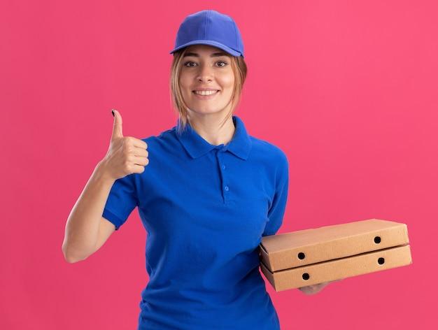 制服を着た笑顔の若いかわいい配達の女性は、ピンクの壁に隔離されたピザの箱と親指を保持します