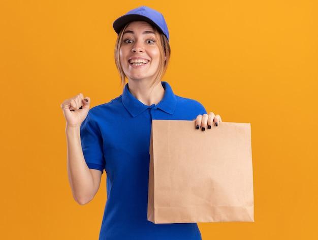 Улыбающаяся молодая симпатичная женщина-доставщик в униформе держит кулак и держит бумажный пакет, изолированный на оранжевой стене