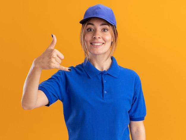 Sorridente giovane donna graziosa di consegna in uniforme facendo appendere sciolto gesto isolato sulla parete arancione