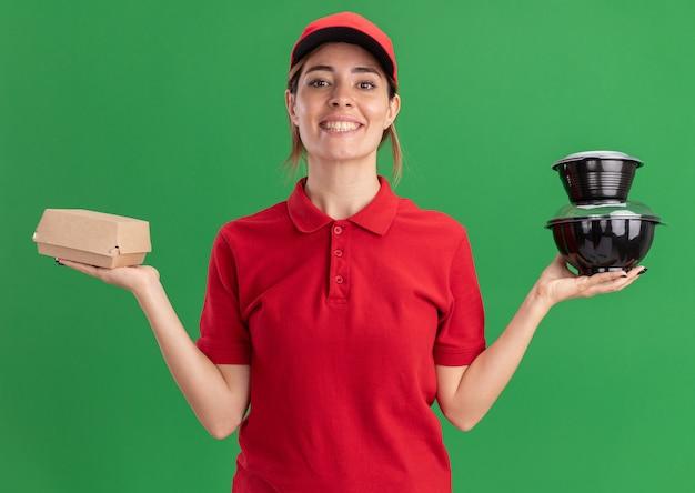 La giovane donna graziosa di consegna sorridente in uniforme tiene i contenitori di cibo e il pacchetto dell'alimento che esamina la parte anteriore isolata sulla parete verde