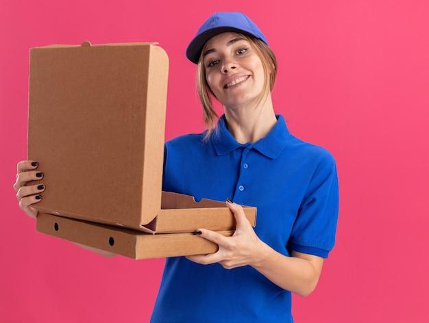 Sorridente giovane donna graziosa consegna in uniforme tiene scatole per pizza isolate sulla parete rosa
