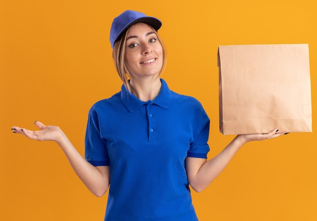Smiling young pretty delivery woman in uniform keeps hand open and holds paper package isolated