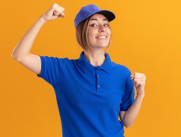Sorridente giovane donna graziosa di consegna in uniforme sta con i pugni alzati isolati sulla parete arancione
