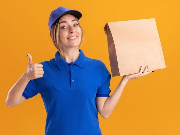 Sorridente giovane donna graziosa di consegna in uniforme pollice in alto e tiene il pacchetto di carta isolato sulla parete arancione