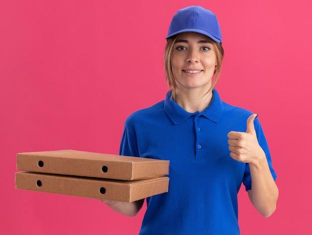 Sorridente giovane donna graziosa di consegna in uniforme pollice in alto e tiene scatole per pizza isolate sulla parete rosa