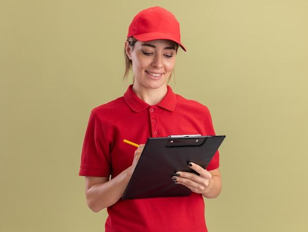 La giovane donna graziosa di consegna sorridente in uniforme scrive negli appunti con la penna isolata sulla parete verde oliva
