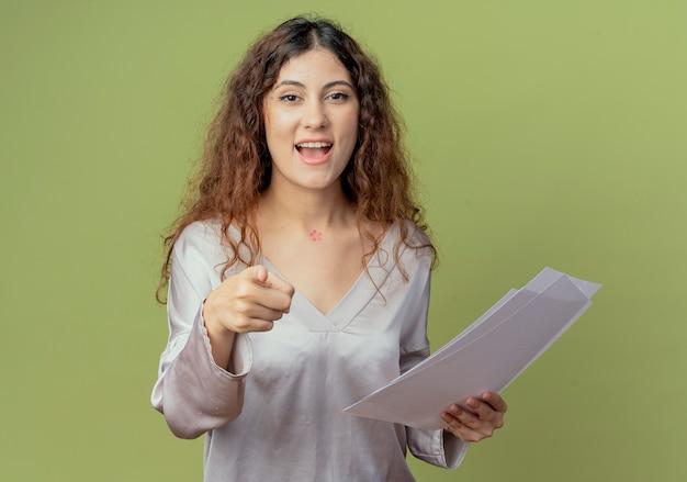 Sorridente giovane impiegato abbastanza femminile in possesso di documenti e mostrandoti gesto isolato su verde oliva