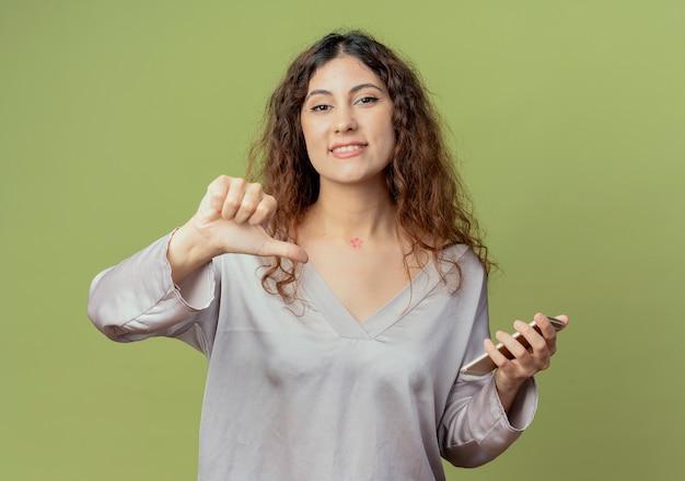 Sorridente giovane impiegato abbastanza femminile che tiene il telefono e il suo pollice verso il basso isolato su verde oliva