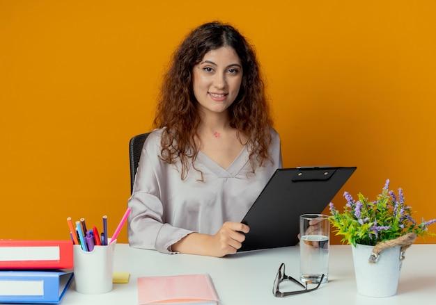 Улыбающийся молодой симпатичный женский офисный работник, сидящий за столом с офисными инструментами, держащий буфер обмена, изолированный на оранжевом
