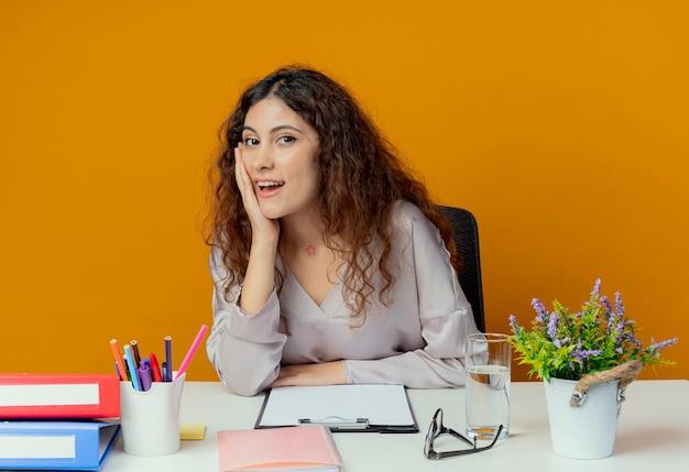 オレンジ色に分離された頬に手を置く事務ツールと机に座っている若いきれいな女性サラリーマンの笑顔
